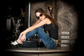 Hot and stylish brunette in sun glasses on a bar table — Stock Photo