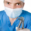 A dentist with medical forceps — Stock Photo