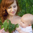 Beautiful mother with a baby in a garden — Stock Photo