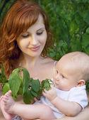 Güzel bir bahçede bir bebekle anne — Foto de Stock