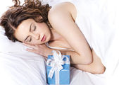 Beautiful young woman sleeping on the bed with presents — Stock Photo