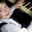 Stock Photo: Little boy and piano.
