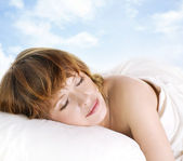 Beautiful young woman sleeping in white bed — Stock Photo