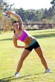 Beautiful Brunette Ahtlete Stretches Outdoors (4) — Stock Photo