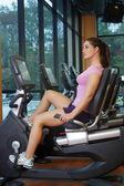 Beautiful Female Athlete on a Cycling Machine (3) — Stock Photo
