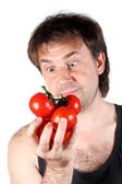 The man looking at tomatoes on a white background — Stock Photo