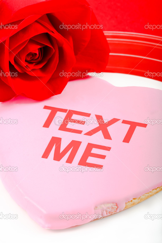 A pink cookie and red rose use the tech-oriented phrase Text Me to send a flirtatious message to a loved one.  Stock Photo #8626389
