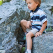 Sad boy sitting on rock. — Stock Photo