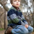 Little boy sitting on the tree stump, fall, park — Stock Photo