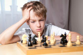 Pensive teenager playing chess — Stock Photo