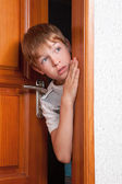 Surprised boy peeks from behind door — Stock Photo