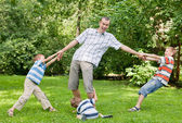 Father and three sons play in the park. — Stock Photo