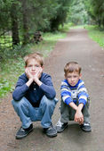 Two serious brother sitting on edge of road — Stock Photo
