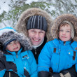 Father and two sons in  winter forest — Stockfoto