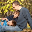 Royalty-Free Stock Photo: Father and two sons sitting on fallen leaves in the park