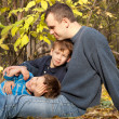 Father and two sons sitting on fallen leaves in the park — Stock Photo