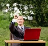 Człowiek z laptop działa na zewnątrz w sieci społecznej — Zdjęcie stockowe