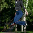 Jumping woman with skipping rope at park - Stockfoto