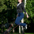 Royalty-Free Stock Photo: Jumping woman with skipping rope at park