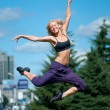 Woman dancing over green city street — Stock Photo
