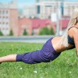 Young woman doing stretching exercise on grass - Stock Photo