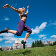 Woman dancing over green city street - Stock Photo