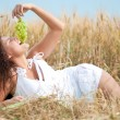 Perfect woman eating grapes in wheat field. Picnic. — Stock Photo