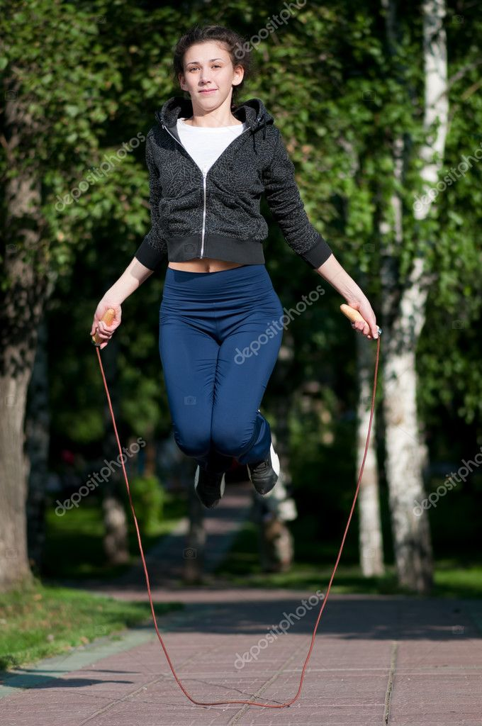 Beautiful young woman doing  exercise with skipping rope at park. Jumping  Stock Photo #8457782