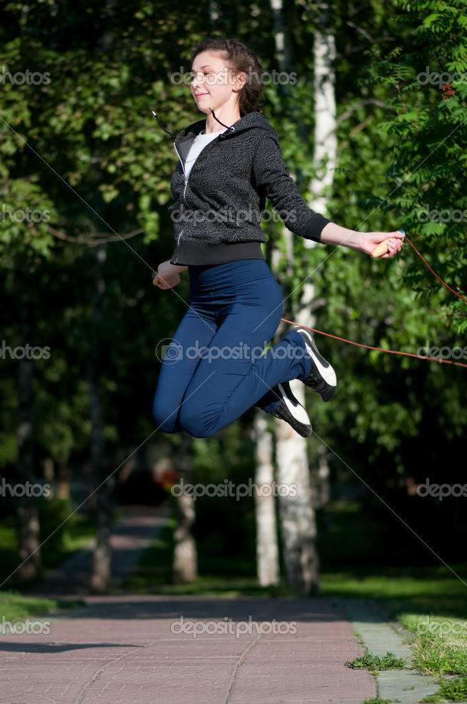 Beautiful young woman doing  exercise with skipping rope at park. Jumping  Stock Photo #8457827