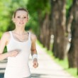 Young woman running in green park — Stock Photo #8462124