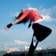 Woman dancing hip hop over blue sky — Stock Photo