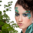 Close-up of sprite girl with faceart and plant - Stock Photo