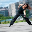Beautiful girl dancing hip-hop over urban landscape — Stock Photo #8467661