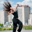 Beautiful girl dancing hip-hop over urban landscape — Photo