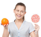 Pretty young woman with lollipop and orange. Choice — Stock Photo
