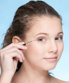 Young beautiful girl doing make-up by brush — Stock Photo