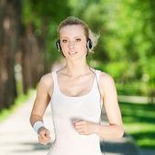 Joven mujer que corre en el parque verde — Foto de Stock