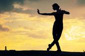 Sylwetka taniec kobiety na zachód słońca. joga — Zdjęcie stockowe