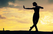 силуэт танцы женщины над закат. йога — Стоковое фото