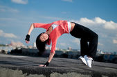 Woman dancing hip hop over blue sky — Stock Photo
