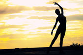 Silhouette of dancing woman over sunset. Yoga — Stock Photo