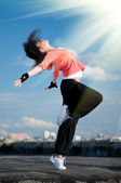 Woman dancing hip hop over blue sky and sun — Stock Photo