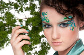 Close-up of sprite girl with faceart and plant — Stock Photo