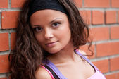 Beautiful teenage girl pose over brick wall — Stock Photo