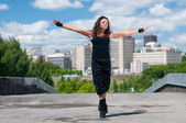 Beautiful girl dancing hip-hop over urban landscape — Stock Photo