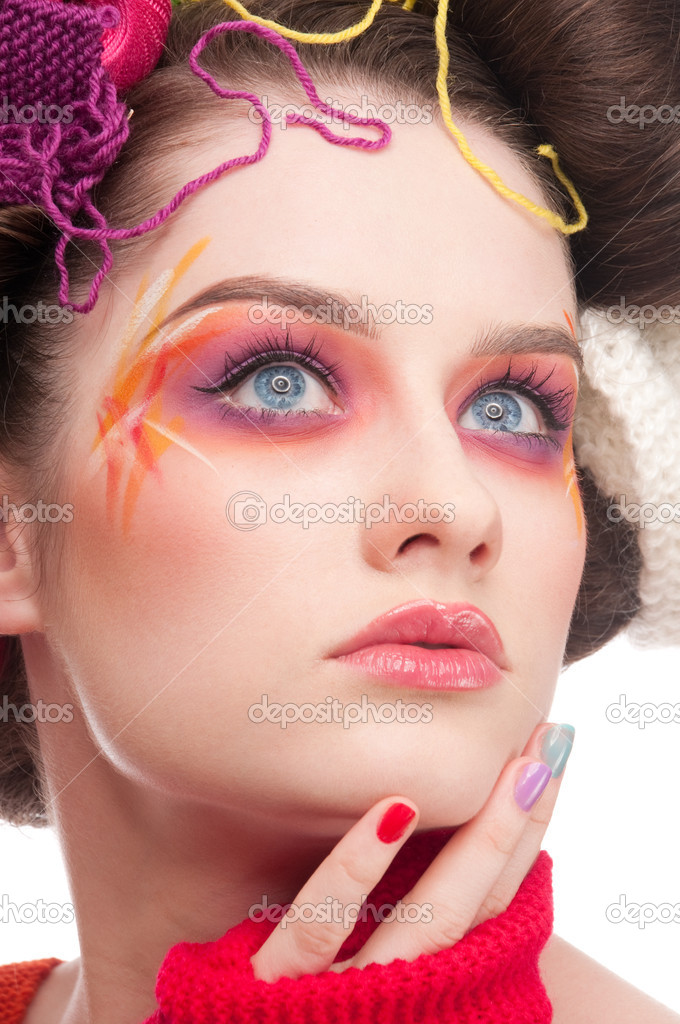 Closeup portrait of beautiful fashion woman with color face art. All in knitting style. Wool balls.  Photo #8466491
