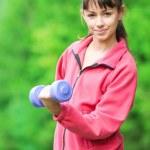 Girl doing dumbbell exercise outdoor — Stock Photo #8529881