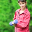 Girl doing dumbbell exercise outdoor — Stock Photo