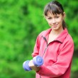 Girl doing dumbbell exercise outdoor — Stock Photo #8529980