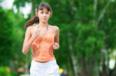 Teenage girl running in green park — Stock Photo